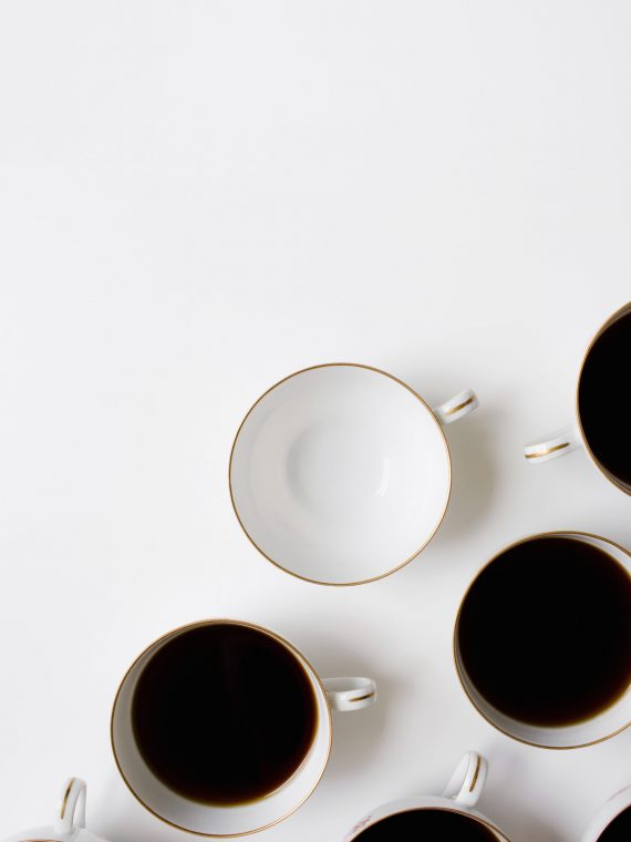 assorted coffee cups filled with black coffee, one is empty
