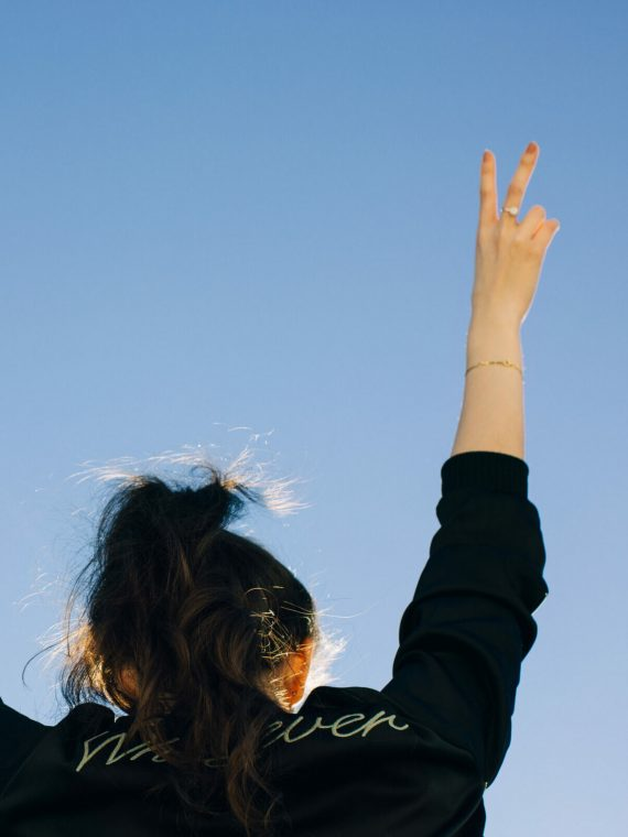 Young Rebel Girl Wearing Bomber Jacket With The Word Whatever And Showing Peace Sign